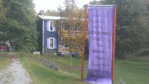 A banner displaying the word 'peace' in several languages greets visitors at the farm of Myra Bonhage-Hale