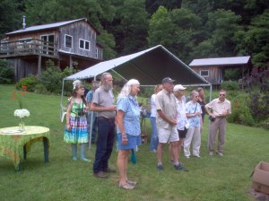 Folks listen to homeowner Autumn Long talk about their solar-powered home, which is in the background